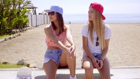 Two trendy young women with skateboards. Two trendy young women wearing skimpy shorts and baseball caps sitting on a seafront wall with skateboards looking to stock footage