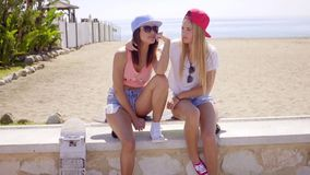 Two trendy young women with skateboards. Two trendy young women wearing skimpy shorts and baseball caps sitting on a seafront wall with skateboards looking to stock video footage
