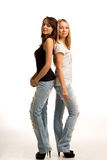 Two trendy young women standing back to back Royalty Free Stock Photo