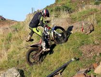 Trial motorcyclist going up a hill Royalty Free Stock Image
