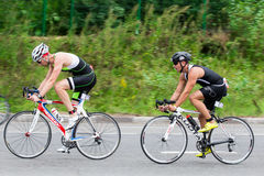 Two triathletes ride speed cycles during triathlon competition Stock Photography