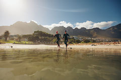 Two triathletes running into the water Stock Photography