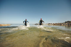 Two triathletes rushing into water for swim portion of race Stock Photo