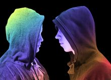 Two troubled teenage boys with black hoodie standing in front of each other in profile isolated on black background. Creative colo royalty free stock image