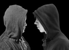 Two troubled teenage boys with black hoodie standing in front of each other in profile isolated on black background. Black and whi royalty free stock image