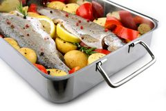 Two trout with potatoes and peppers on baking sheet Royalty Free Stock Photo
