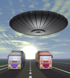 Two trucks carrying cargo are on the highway and round UFO over Royalty Free Stock Image