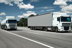 Two trucks with container and cistern on road, cargo transportation concept stock photography