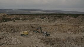 Two trucks and excavator in a quarry. Excavator working in a quarry. Two trucks and excavator stock footage