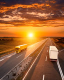 Two trucks on the highway at sunset Royalty Free Stock Image