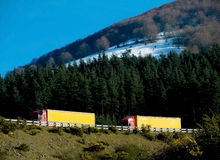 Two trucks on mountain road. Trucks crossing spanish mountain road with snow and blue sky Stock Photo
