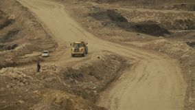 Two trucks on a road near quarry. Day country side, dirt road driving stock footage
