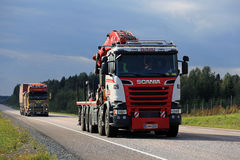 Two Trucks Trucking Under Dark Sky. ORIVESI, FINLAND - SEPTEMBER 1, 2016: Scania crane truck of Kurko-Koponen Oy and another rig trucking along the road under Royalty Free Stock Images