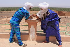 Two Tuaregs in blue dress and white turbans playing game Stock Images