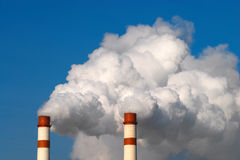 Two tubes. Two huge steaming plant power plant tubes over blue sky Royalty Free Stock Image