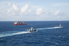 Two Tugs and Orange Tanker on Blue Sea Stock Photos