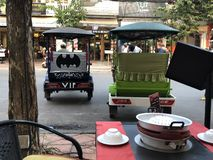 Cambodia Siem Reap Black VIP Batman Tuk Tuk is parked next to green one on Main Street royalty free stock photos