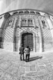 Two turists admire the Jabalquinto palace entrance, Baeza Stock Image