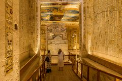 Two turists in the interior of a tomb in the valley of the kings royalty free stock image