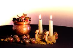 Two turkey candle holders with lit candles burning next to a copper filled with red and gold apples spilling out from it stock image
