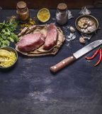 Two turkey steak with a knife with a variety of seasonings lemon garlic and hot red pepper parsley with text area on wooden rustic Stock Images