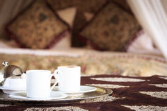 Two turkish coffee cups with oriental canopy bed at the backgrou Royalty Free Stock Photography