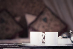 Two turkish coffee cups with oriental canopy bed at the backgrou Royalty Free Stock Images