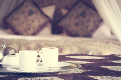 Two turkish coffee cups with oriental canopy bed at the backgrou Stock Images
