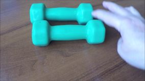Two turquoise dumbbells. On the table stock video