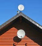 Two TV satellite dishes on wall and roof of wooden house royalty free stock photos