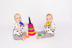 Two twin babies 8 months old play on a white isolated background, early development of children up to a year old, a child takes a