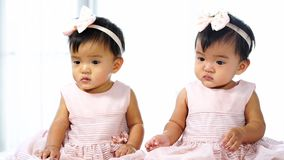Two twin babies in pink dress on bed. Two twin babies in pink dress on a bed stock video