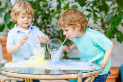Two twin boys making experiment with colorful bubbles Royalty Free Stock Images