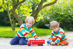 Two twin boys playing with red school bus Stock Photos