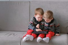 Two twin brothers take away each other`s tablet sitting on the sofa. Kids play games on the tablet. royalty free stock photos