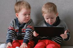 Two twin brothers take away each other`s tablet sitting on the sofa. Kids play games on the tablet. stock photos
