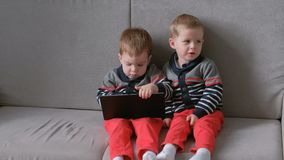 Two twin brothers take away each other`s tablet sitting on the sofa. Kids play games on the tablet. Two twin brothers take each other`s tablet sitting on the stock video footage