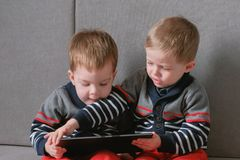 Two twin brothers take away each other`s tablet sitting on the sofa. Kids play games on the tablet. Two twin brothers take each other`s tablet sitting on the stock photography