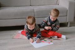 Two twin brothers toddlers draw together markers sitting on the floor. Two twin brothers toddlers draw together markers sitting on the floor royalty free stock photography