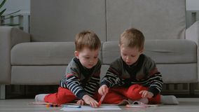 Two twin brothers toddlers draw together markers sitting on the floor. Two twin brothers toddlers draw together markers sitting on the floor stock footage