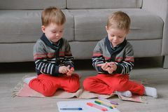Two twin brothers toddlers draw together markers sitting on the floor. Two twin brothers toddlers draw together markers sitting on the floor royalty free stock images