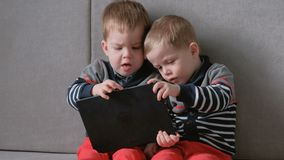 Two twin brothers toddlers playing together games on tablet sitting on the sofa. Two twin brothers toddlers playing together games on tablet sitting on the sofa stock video