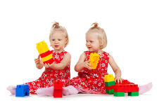 Two twin girls in red dresses playing with blocks. Children and twins concept - two identical twin girls in red dresses playing with toy blocks royalty free stock photography