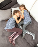 Two twin girls sleeping on couch Royalty Free Stock Images