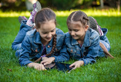 Two twin girls using tablet at park Stock Photos
