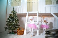 Two twin sisters in doggie dresses at the front of a white wooden house are playing. Girls and poodles decorated for Christmas and. New Year royalty free stock images