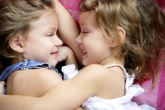 Two twin sisters in a hug, close up Stock Photos