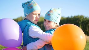 Two twin sisters hugging and kissing. Children hold balloons. Two twin sisters embrace and kiss stock footage