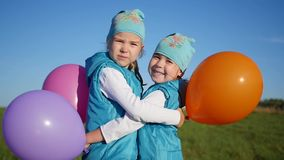 Two twin sisters hugging and kissing. Children hold balloons. Two twin sisters embrace and kiss stock video footage