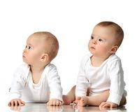 Two twin sisters infant child baby girls toddler sitting in white shirt looking at the corner stock images